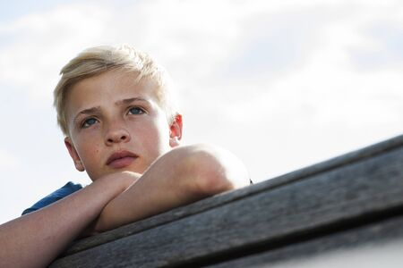 leaned: Close-up portrait of boy outdoors,looking into the distance,Germany