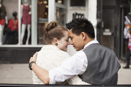 tenderly: Close-up, backview of couple sitting on bench on city street, Toronto, Ontario, Canada