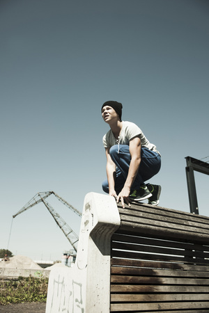 Teenager crouching down on barrier,anticipating next move,freerunning,Germany
