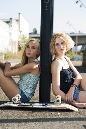 leaned: Portrait of teenage girls outdoors with skateboard,looking at camera,sitting on street,Germany