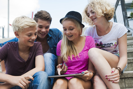 10 15 years: Group of teenagers sitting on stairs outdoors,looking at tablet computer,Germany