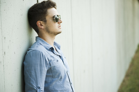 leaned: Side view portrait of young man leaning against wall of building,wearing sunglasses,Germany