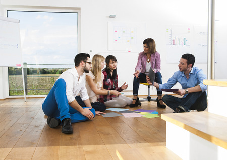 conferring: Mature businesswoman meeting with group of young business people, sitting on floor in discussion, Germany
