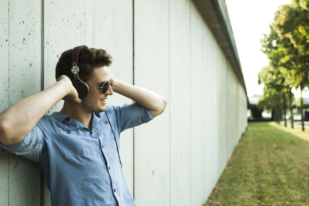 leaned: Young man standing outside leaning on wall of building,wearing headphones and sunglasses,Germany