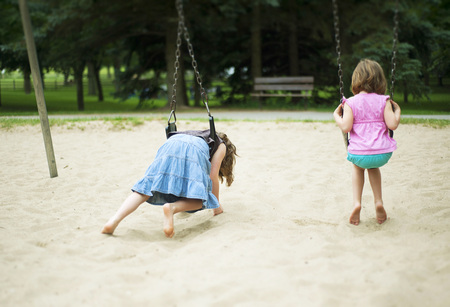 leaned: Back View of Girls on Swings,Thomson Memorial Park,Scarborough,Ontario,Canada LANG_EVOIMAGES