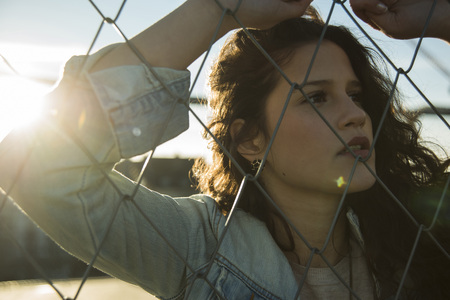 leaned: Close-up portrait of teenage girl standing outdoors next to chain link fence, Germany