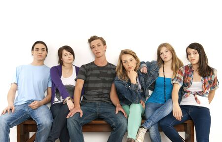 leaned: Portrait of six young people sitting together on a bench, studio shot on white background