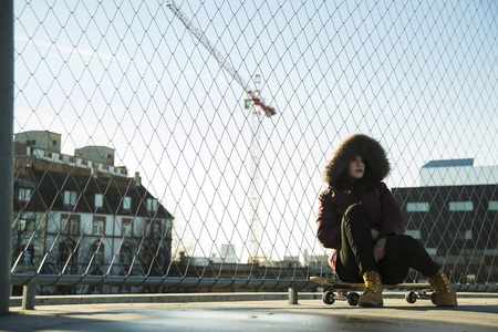 leaned: Teenage girl wearing winter coat, sitting on skateboard outdoors, next to chain link fence near comercial dock, Germany