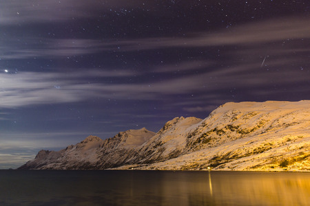 nightime: Starry night sky with moon illuminating snow covered mountains at a fjord in the Arctic, Norway