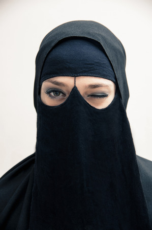 subservience: Portrait of young woman in black, muslim hijab and muslim dress, winking at camera, eyes with makeup, on white background LANG_EVOIMAGES