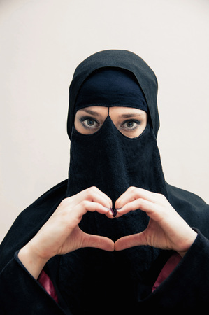 Portrait of young woman in black, muslim hijab and muslim dress, making heart shape with hands, on white background LANG_EVOIMAGES