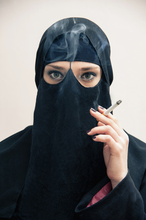 subservience: Portrait of young woman in black, muslim hijab and muslim dress, holding cigarette and smoking, on white background