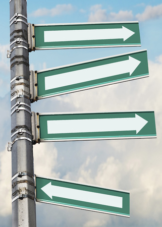 Arrow signs on a pole, showing different directions against sky