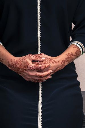 subservience: Woman sitting down with close-up of folded hands painted with henna in arabic style, wearing black, arabic, muslim dress LANG_EVOIMAGES