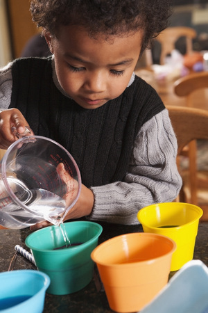 Boy Pouring Water into Dye Cups for Coloring Easter Eggs LANG_EVOIMAGES