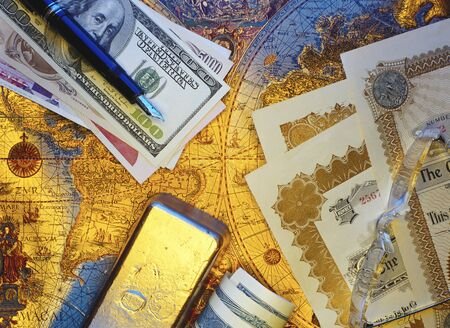 International Currency, Pen Stock Certificates and Gold Bar On Antique World Map