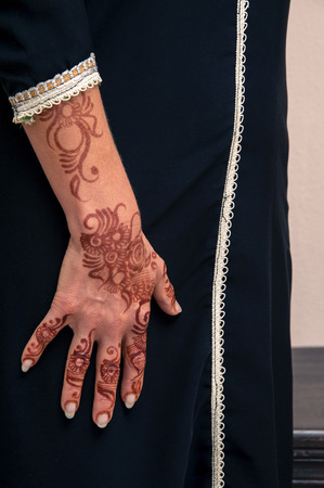 subservience: Woman standing with close-up of arms and hand painted with henna in arabic style, wearing black, arabic, muslim dress LANG_EVOIMAGES