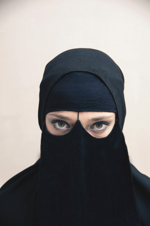 subservience: Portrait of young woman in black, muslim hijab and muslim dress, eyes looking at camera with eye makeup, on white background