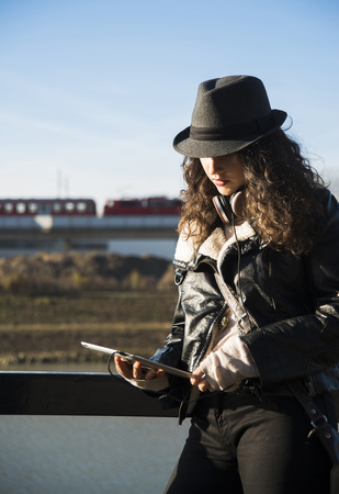 leaned: Teenage girl standing outdoors, wearing fedora and using tablet computer, Germany LANG_EVOIMAGES