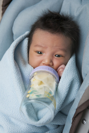 lying forward: Close-up of swaddled two week old, newborn Asian baby girl, lying in car seat drinking from baby bottle