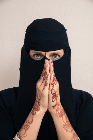 subservience: Portrait of woman in black muslim hijab and muslim dress, hands praying and painted with henna in arabic style