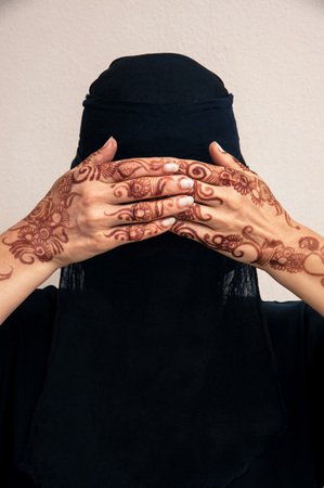 subservience: Portrait of woman in black muslim hijab and muslim dress, hands covering eyes and painted with henna in arabic style LANG_EVOIMAGES