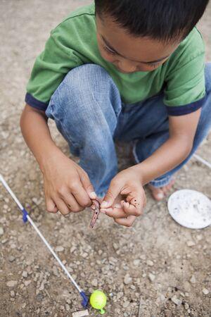 Crouching Boy preparing Worm for Fishing, Lake Fairfax, Reston, Virginia, USA LANG_EVOIMAGES