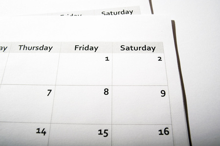 Close-up of pages from a monthly calendar showing days of the week, studio shot