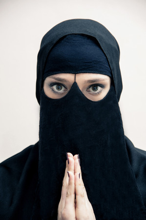 subservience: Portrait of young woman in black, muslim hijab and muslim dress, with hands praying, looking at camera, on white background