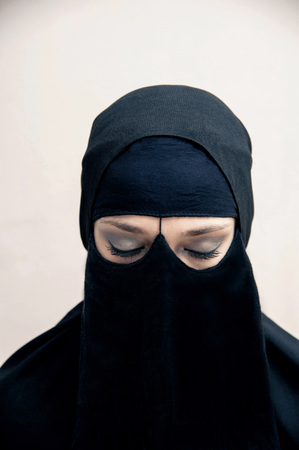 societal: Portrait of young woman in black, muslim hijab and muslim dress, eyes closed with eye makeup, studio shot on white background