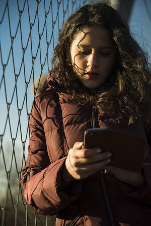 leaned: Close-up of teenage girl standing next to chain link fence, wearing winter coat and using smart phone, Germany