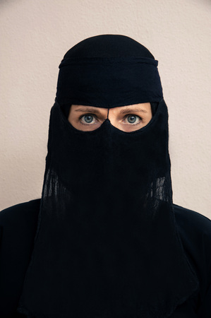 subservience: Close-up portrait of woman wearing black muslim hijab and muslim dress, looking at camera, studio shot on white background