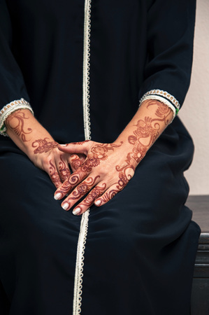 subservience: Woman sitting down with close-up of arms and hands painted with henna in arabic style, wearing black, arabic, muslim dress