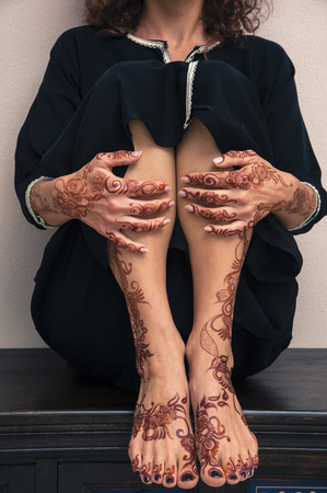 subservience: Low section of woman showing legs, feet and hands painted with henna in arabic style, wearing black, arabic, muslim dress
