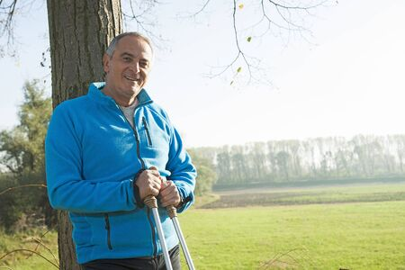 leaned: Senior Man with Nordic Walking Poles by Tree, Mannheim, Baden-Wurttemberg, Germany