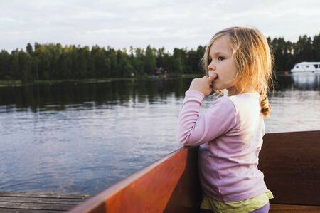 leaned: 3 year old girl standing in a docked motorboat, looking at the lake, Sweden