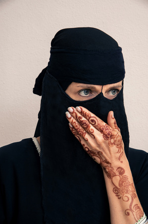 subservience: Portrait of woman in black muslim hijab and muslim dress, hand covering mouth, hands painted with henna in arabic style