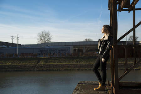 leaned: Teenage girl standing on commercial dock outdoors, looking into the distance, Germany LANG_EVOIMAGES