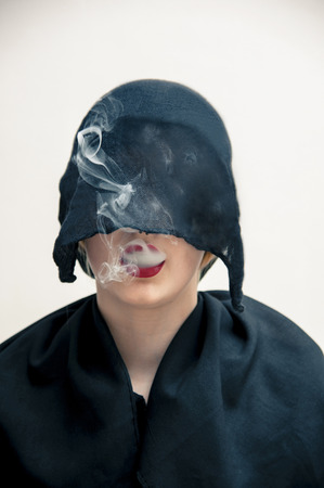 subservience: Portrait of young woman in black, muslim dress and black, hijab covering part of head, while blowing smoke from red lips