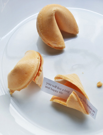 goodluck: Close up of fortune cookies on white plate, showing text for long, happy life, studio shot LANG_EVOIMAGES