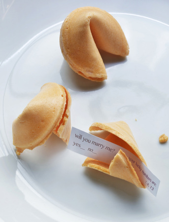 goodluck: Close-up of fortune cookies on white plate, showing text for marriage proposal, studio shot