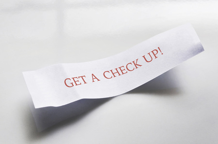 innuendo: Close-up of message from fortune cookie on white plate, showing text for medical checkup, studio shot on white background LANG_EVOIMAGES