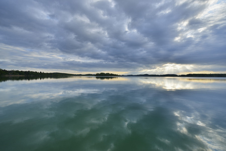 Clouds and crepuscular sunrays refelcted in lake at sunrise, Woerthsee Lake, Upper Bavaria, Fuenfseenland, Germany LANG_EVOIMAGES