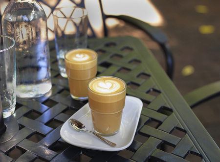 Two cortado coffees in glasses on outdoor, patio table with water bottle and glass, Canada