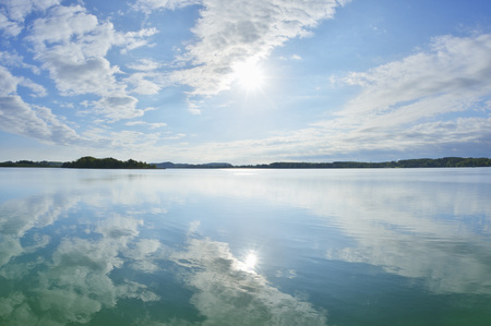 Blue sky, clouds and sun reflected in lake, Lake Woerthsee, Bavaria, Germany LANG_EVOIMAGES