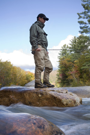Man finds a fly fishing hole, standing on rocks along river, New Hampshire, USA LANG_EVOIMAGES