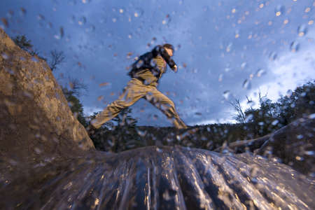 adventuresome: Low angle view of man jumping across river while hiking in New Hampshire, USA