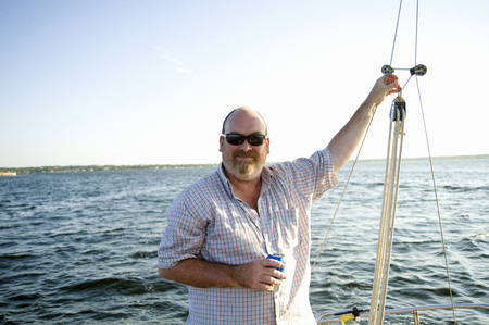 leaned: Mature Man on Sailboat holding canned Beverage and Smiling, Shediac Bay, New Brunswick, Canada