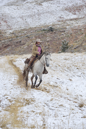 adventuresome: Cowgirl riding horse in snow, Rocky Mountains, Wyoming, USA