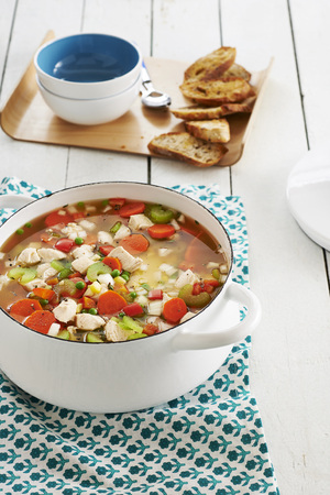 Chicken and vegetable soup in a stock pot with bread and bowls in the background, studio shot